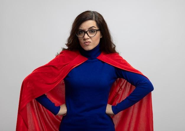 Chica superhéroe caucásica enojada con capa roja en gafas ópticas pone las manos en la cintura