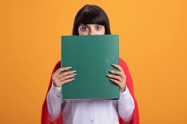 Chica superhéroe joven sorprendida con estetoscopio con bata médica y capa cubierta con la cara con carpeta