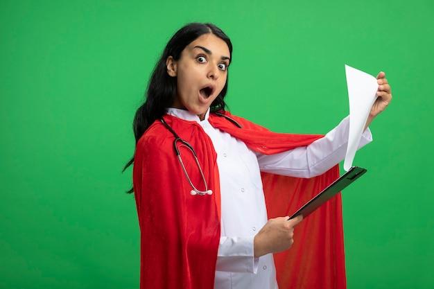 Chica superhéroe joven sorprendida mirando al frente vistiendo bata médica con estetoscopio sosteniendo y hojeando a través del portapapeles aislado en verde