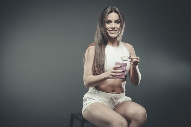 Chica con suplemento de batido de proteína de suero en polvo