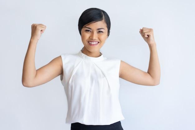 Chica tailandesa alegre mostrando fuerza