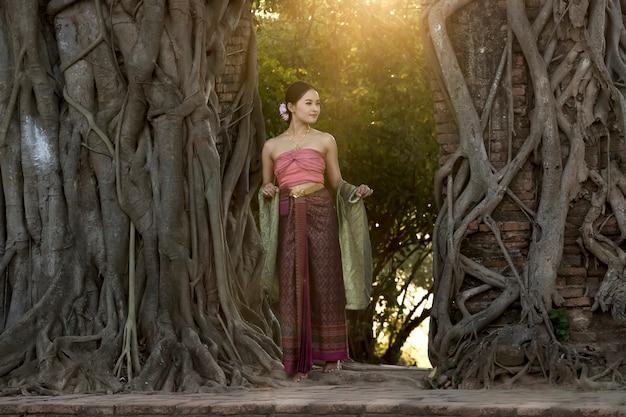 Chica tailandesa en traje tradicional tailandés con templo ayutthaya