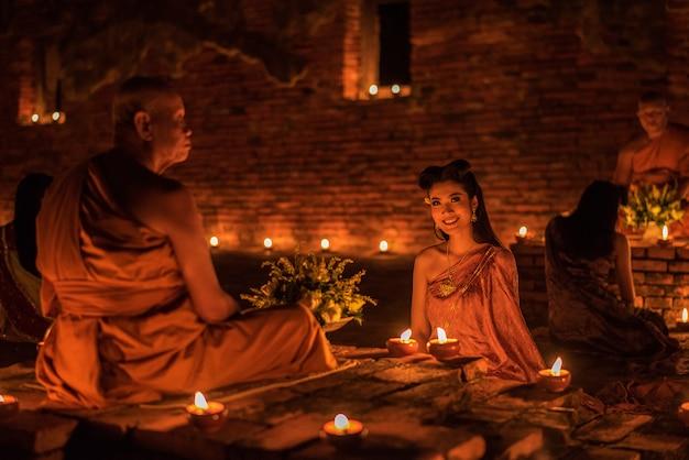 Chica tailandesa en traje tradicional tailandés en el templo por la noche