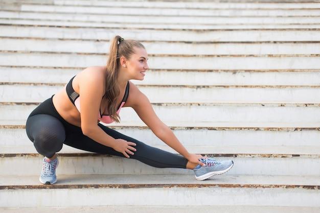 Chica de talla grande alegre en top deportivo y leggings felizmente estirándose en las escaleras mientras pasa tiempo al aire libre