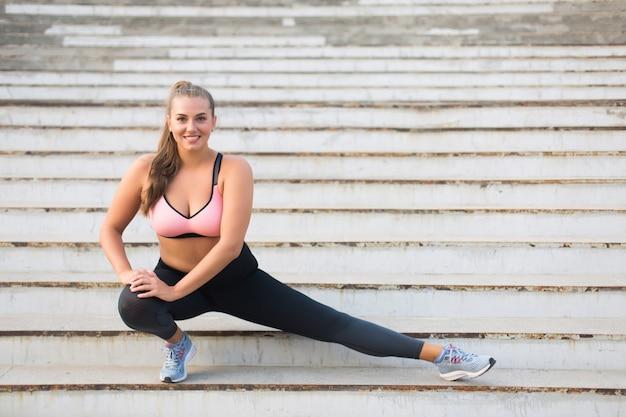 Chica de talla grande muy sonriente en top deportivo y leggings haciendo deporte en las escaleras felizmente mientras pasa tiempo al aire libre