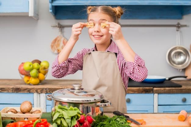 Chica tapándose los ojos con pasta farfalle de pie en la cocina