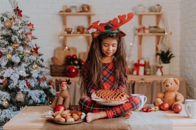 Chica con tarta de navidad en la cocina decorada invierno cuento de año nuevo fiesta de té familiar tiempo de higiene