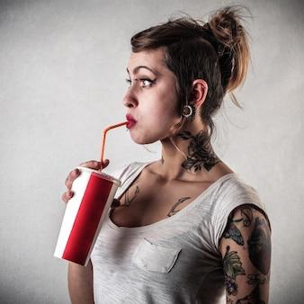 Chica tatuada bebiendo un refrescante