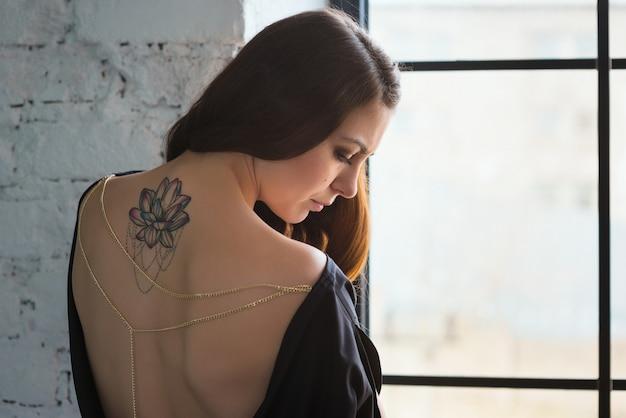 Chica con tatuaje de loto en la espalda triste en la ventana