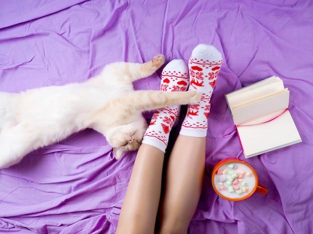 Chica con una taza de café, próximo libro, ambiente navideño, calcetines para navidad
