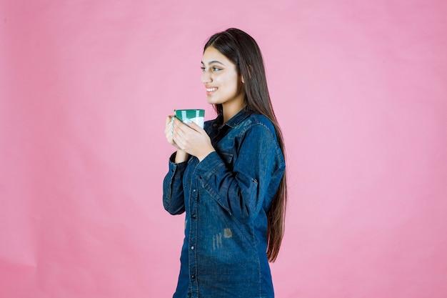 Chica con una taza de café sonriendo y sintiéndose positivo