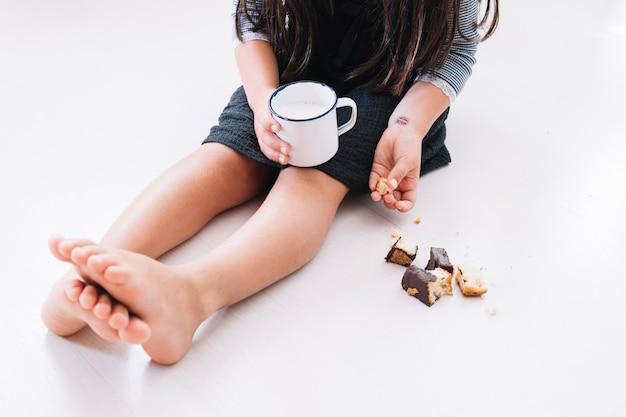 Chica con taza de leche y galletas
