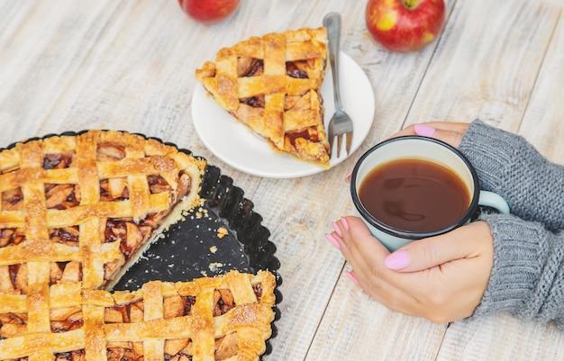 Chica con una taza de té y un pastel con manzanas y canela.