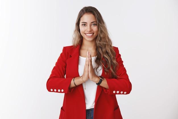 Chica te saluda de manera budista. sonriente atractiva encantadora mujer caucásica de pelo rizado sosteniendo las palmas juntas rezar, sonriendo amable mostrando namaste gesto de bienvenida, invitando a invitados asiáticos a entrar