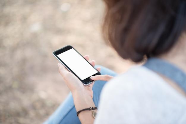 Chica con teléfono inteligente al aire libre en el parque