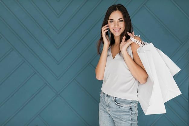 Chica con teléfono inteligente en la oreja y redes de compras en el hombro