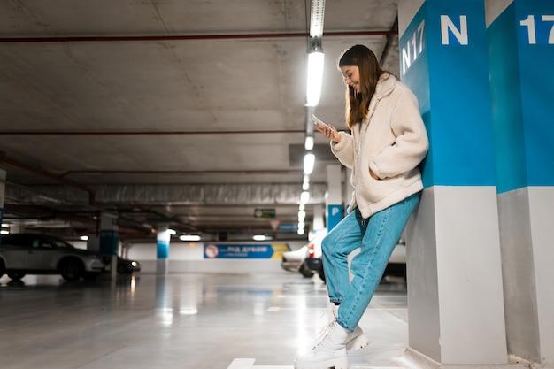 Chica con teléfono móvil en aparcamiento subterráneo.