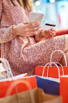 Chica con teléfono móvil y tarjeta de crédito durante las compras en línea