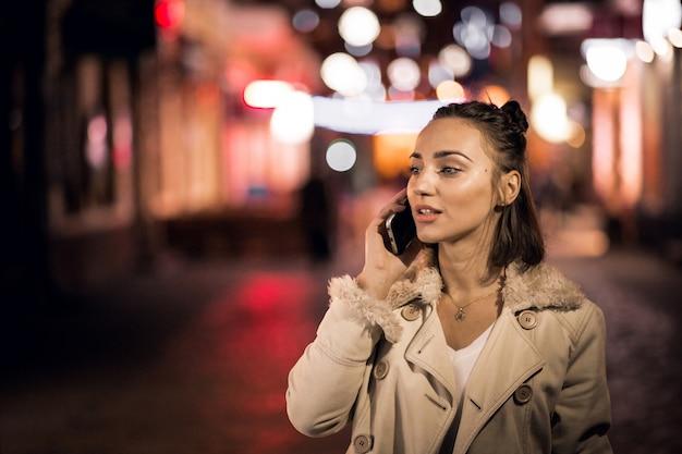 Chica con teléfono en la noche