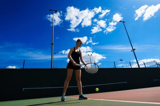 Chica tenista sosteniendo una raqueta de tenis