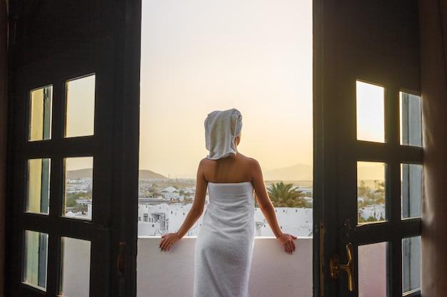 Chica en la terraza en una toalla de baño después de la ducha mira la puesta de sol en las montañas
