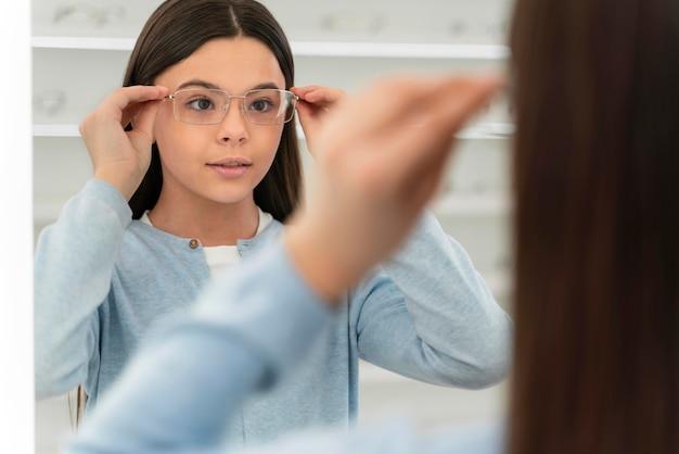 Chica en la tienda de anteojos probándose gafas