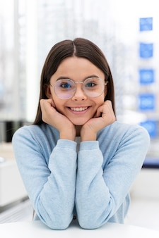 Chica en la tienda probándose gafas