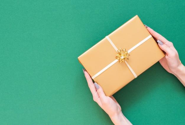 Chica tiene caja de regalo de oro con lazo sobre fondo verde
