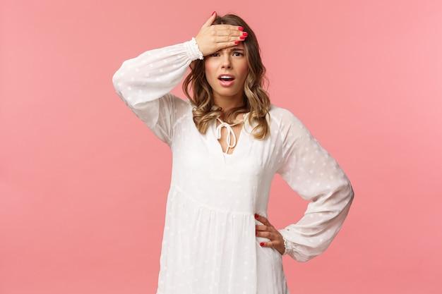 La chica tiene muchos problemas en la cabeza. mujer joven rubia preocupada y preocupada con vestido blanco, con la mano en la frente, mirada desesperada e incómoda.