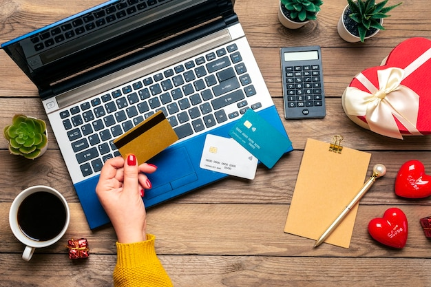 Chica tiene tarjeta de débito, elige regalos, compra, laptop, taza de café, dos corazones, bolsa en mesa de madera