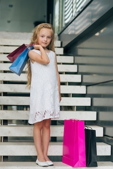 Chica de tiro completo con bolsas de compras