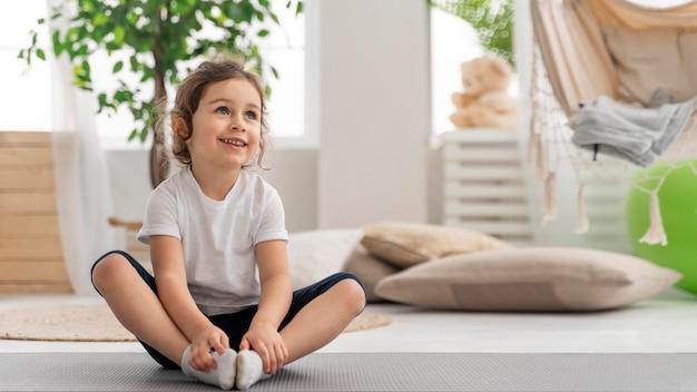 Chica de tiro completo en estera de yoga
