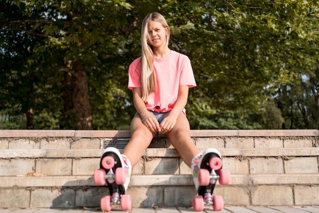 Chica de tiro completo con patines sentado