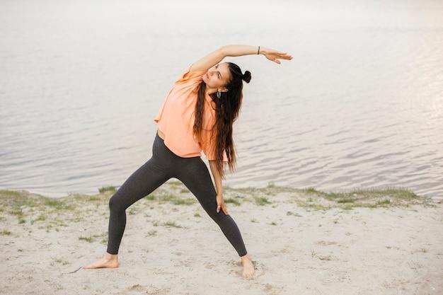 Chica de tiro completo que se extiende cerca del lago