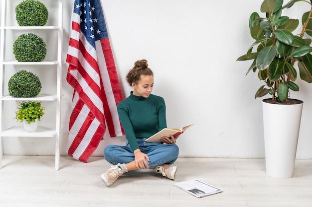 Chica de tiro completo sentada en el suelo y leyendo