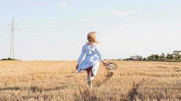 Chica de tiro largo corriendo en un campo