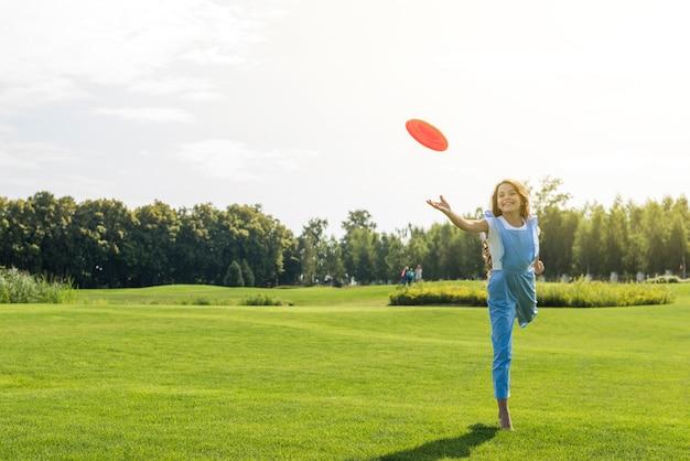 Chica de tiro largo jugando con frisbee