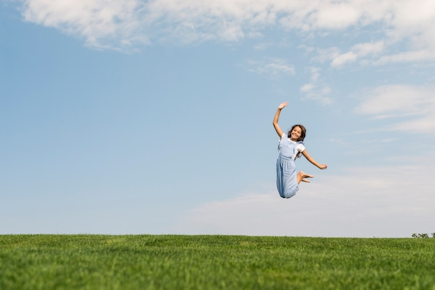 Chica de tiro largo saltando descalzo