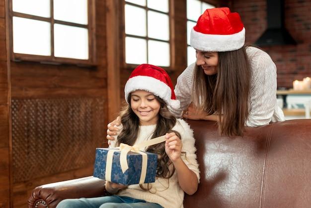 Chica de tiro medio abriendo regalo en el sofá