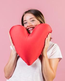 Chica de tiro medio con almohada en forma de corazón