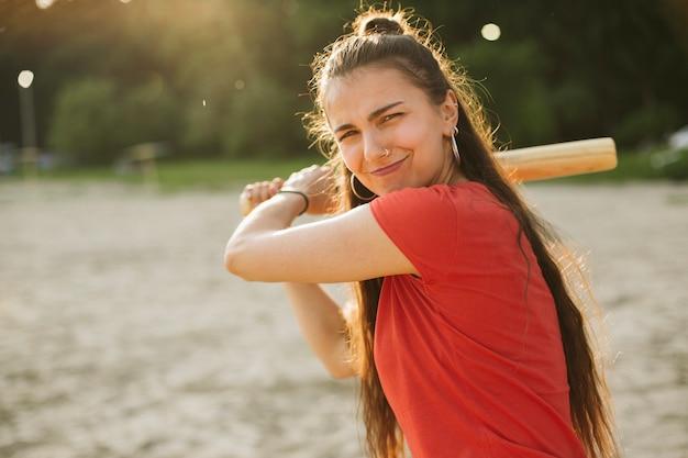 Chica de tiro medio con bate de béisbol posando