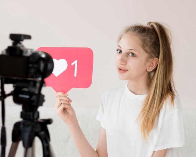 Chica de tiro medio con cámara de video
