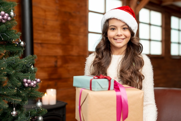 Chica de tiro medio cerca del árbol de navidad mirando a la cámara
