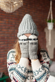 Chica de tiro medio cubriéndose la cara con guantes