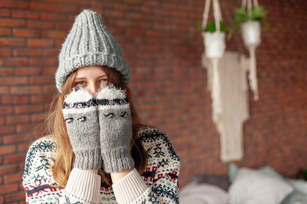 Chica de tiro medio cubriéndose la cara con lindos guantes