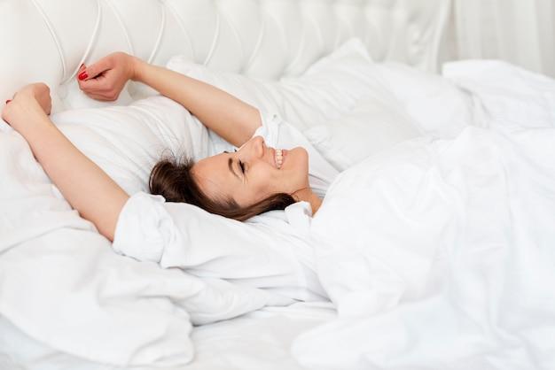 Chica de tiro medio despertando en una cama cómoda