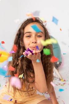 Chica de tiro medio divirtiéndose con confeti