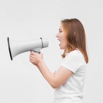 Chica de tiro medio gritando en megáfono