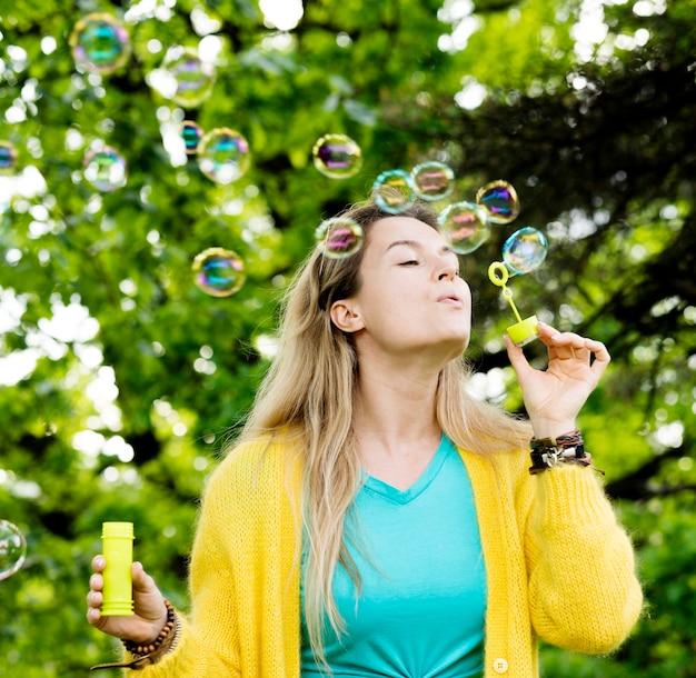 Chica de tiro medio haciendo burbujas