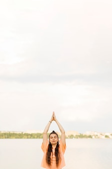 Chica de tiro medio meditando al aire libre